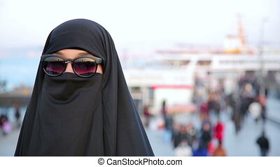 Steadycam - Woman with chador, hijab wearing sunglasses