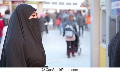 Steadycam - Woman with headscarf, chador using ATM machine