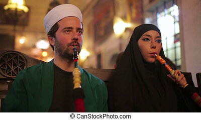 Portrait of islamic couple, smoking shisha