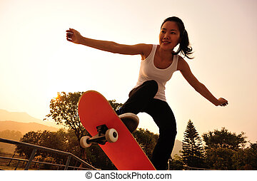young woman skateboarding at sunrise skatepark