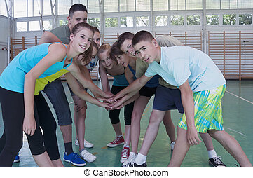 Teens in gymnasium - Young women and men in gym hands in...