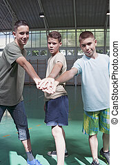 Teens in gymnasium - Young men standing in gymnasium hands...