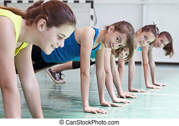Teens in gymnasium - Young women in gym posing for pushups
