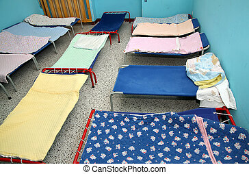 beds and cots in brightly colored dormitory of a nursery -...