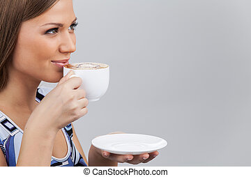 Happy beautiful woman with coffee cup in hands. pretty brunette holding cup and drinking coffee