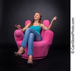 Casual young woman listening to mp3 player. front view of brunette girl sitting in armchair