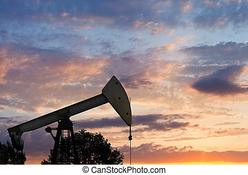 view of pumpjack pumping oil at sunset - view of pumpjack...