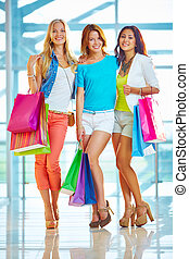 Pretty shoppers - Portrait of three friendly girls looking...