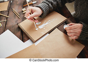 Embodiment of ideas - Close-up of young man hands drawing in...