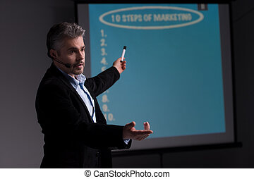 Cheerful trainer pointing at screen with presentation. Young businessman giving presentation and asking his colleagues