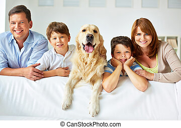 Family on sofa - Smiling family of four with a dog