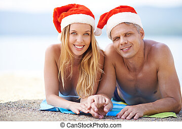 Christmas on the beach - Couple lying on the beach in Santa...
