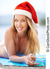 Summer Christmas - Portrait of a woman lying on the beach in...