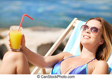 Summer resort - Woman resting in deck chair with a cocktail