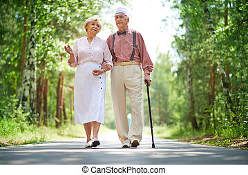 Walking seniors - Senior couple walking in park