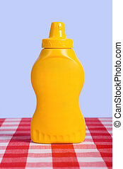 Bottle of Mustard - A yellow squeeze bottle in fornt of a...