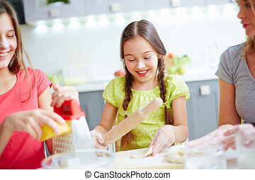Industrious girl - Little girl making dough with her family