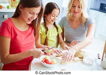 Making pie - Two daughters making an apple pie with their...