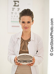 Doctor woman showing eyeglasses in front of snellen chart