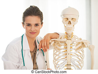 Portrait of doctor woman near human skeleton anatomical...