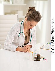 Doctor woman writing in prescription