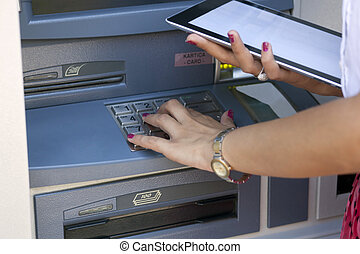 Young woman using ATM machine