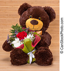 Bear with floral bouquet - Smiling teddy bear holding...