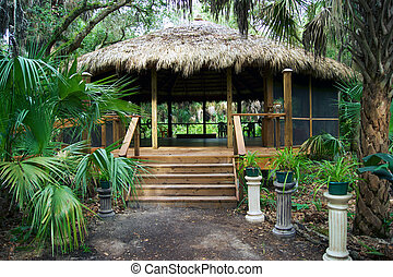 tiki hut building in florida park - Looking up the path to a...