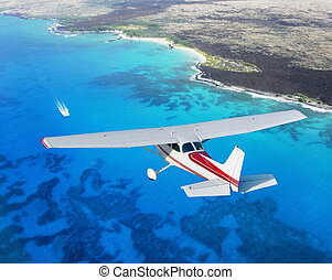 small plane cruising above blue sea
