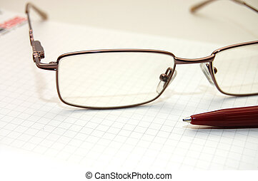 Eye glasses and a pen on sheet