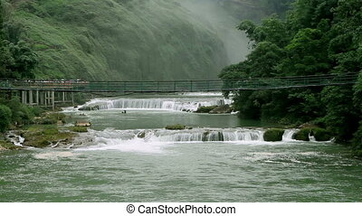 The Huangguoshu Waterfall and the hanging bridge in Guizhou,...