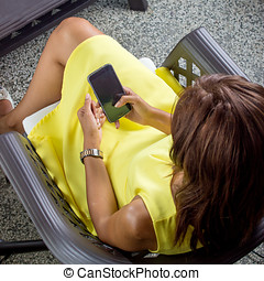 girl in a yellow dress sends sms, from above