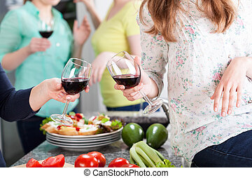 Friends having fun at home with red wine and food