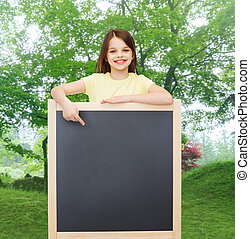 happy little girl pointing finger to blackboard - people,...