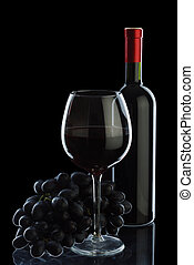 Bottle of wine and grapes isolated on black background