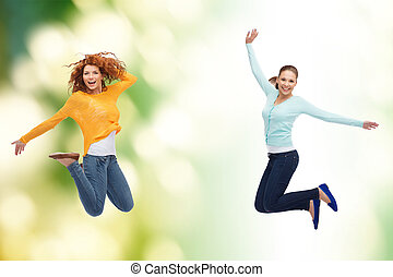 smiling young women jumping in air - happiness, freedom,...