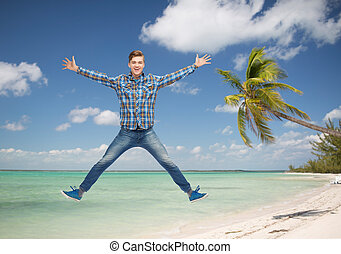 smiling young man jumping in air - summer vacation, travel,...