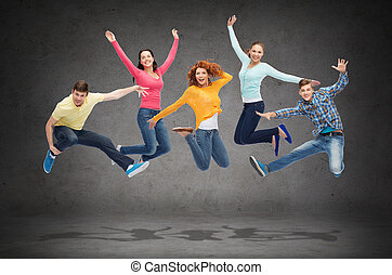 group of smiling teenagers jumping in air - happiness,...