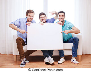happy male friends with blank white board at home -...