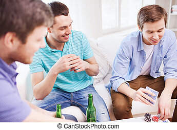 smiling male friends playing cards at home