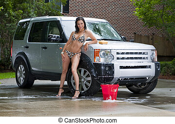 Brunette Model Washing Car - A brunette model washing a...