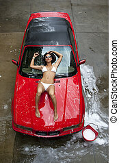 Brunette Model Washing Car - A brunette model washing a red...