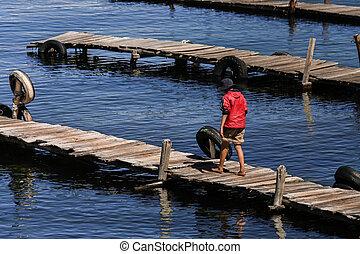Boy walking on pier