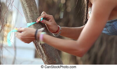 girl decorator tying ribbons on the branches