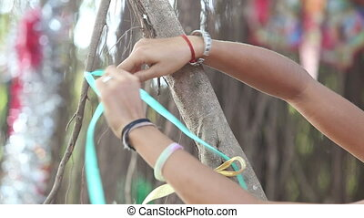 girl decorator tying ribbons on the branches on the Indian...