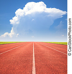 red running track over blue sky and clouds