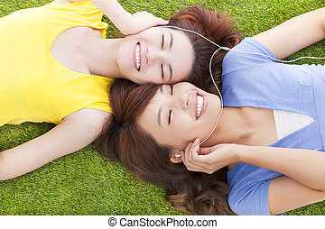 two pretty young woman lying on grassland and listening...