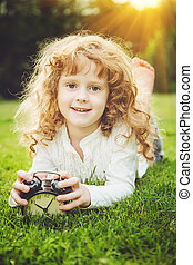 Girl lying on the grass and holding alarm clock.