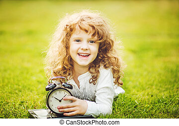 Girl lying on the grass and holding alarm clock