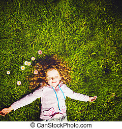 Curly girl lies on the grass and smiling, toning photo